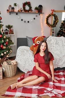 Portrait de jeune femme heureuse détente près de sapin de noël. femme en robe rouge est assis sur plaid le soir de noël à la maison dans le salon. femme à la maison à noël.