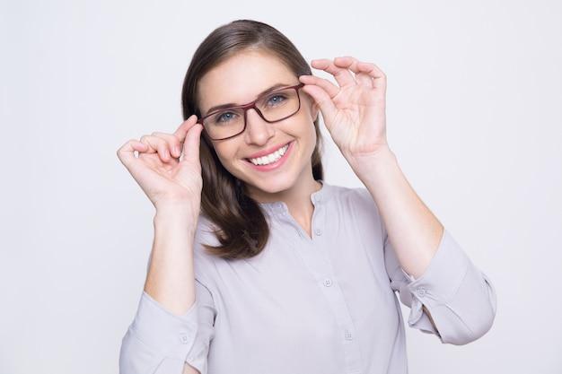 Portrait de jeune femme heureuse d'essayer sur des lunettes