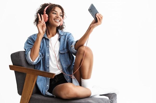 Portrait d'une jeune femme heureuse et excitée écoutant de la musique dans des écouteurs posant isolé sur un mur blanc parlant par téléphone portable prendre un selfie avec paix