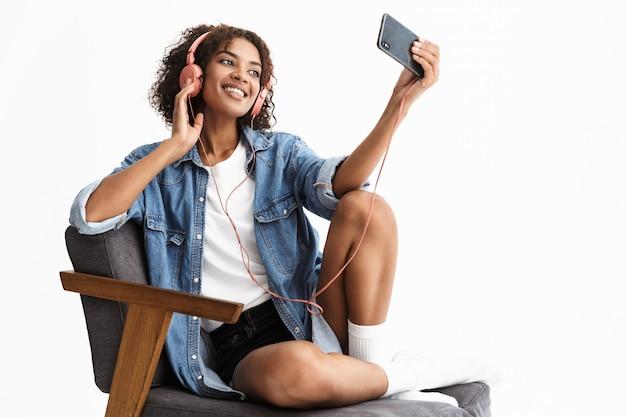 Portrait d'une jeune femme heureuse et excitée écoutant de la musique dans des écouteurs posant isolé sur un mur blanc parlant par téléphone portable prendre un selfie
