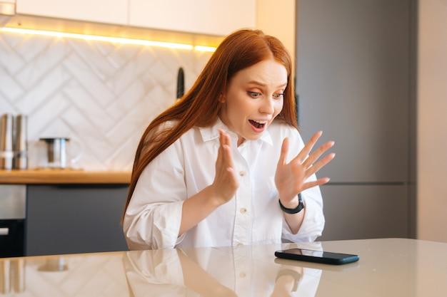 Portrait d'une jeune femme heureuse et excitée qui reçoit des nouvelles en ligne étonnamment bonnes sur un téléphone portable assis