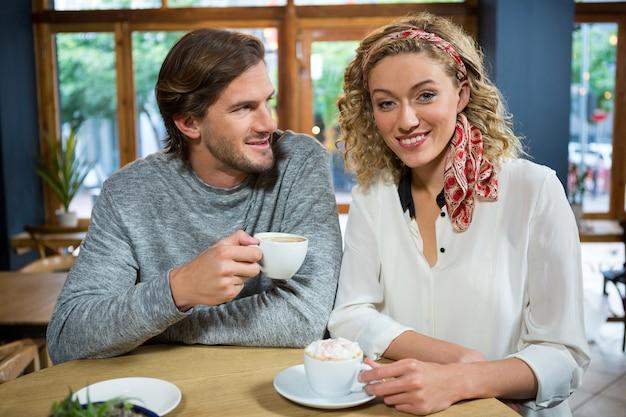 Portrait de jeune femme heureuse avec l'homme à table dans un café