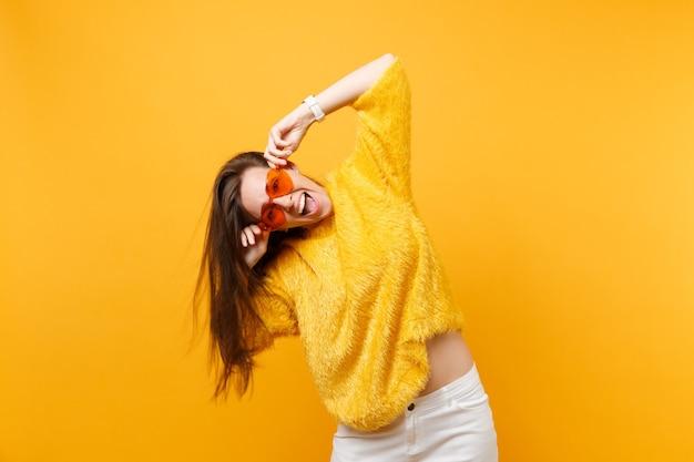 Portrait d'une jeune femme heureuse et joyeuse en pull de fourrure pantalon blanc tenant des lunettes orange coeur isolées sur fond jaune vif. les gens émotions sincères, concept de style de vie. espace publicitaire.