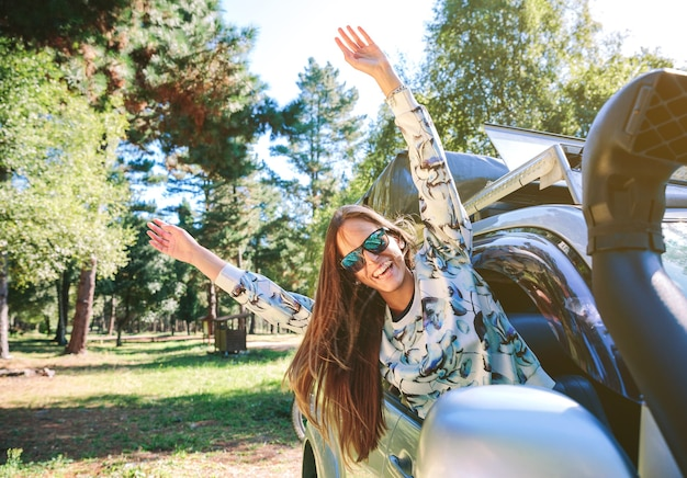 Portrait d'une jeune femme heureuse levant les bras à travers la fenêtre de la voiture par une journée ensoleillée