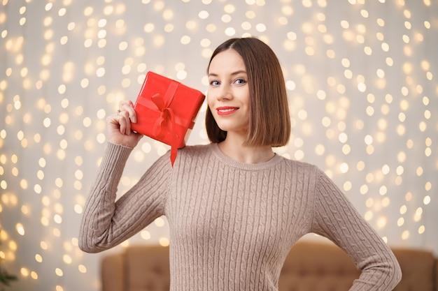 Portrait de jeune femme heureuse lèvres rouges tenant une boîte cadeau emballée.