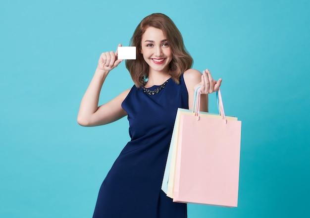 Portrait d'une jeune femme heureuse, montrant la carte de crédit et le sac à provisions isolé sur fond bleu.