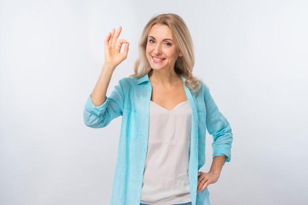 Portrait d'une jeune femme heureuse, montrant le signe ok sur fond blanc