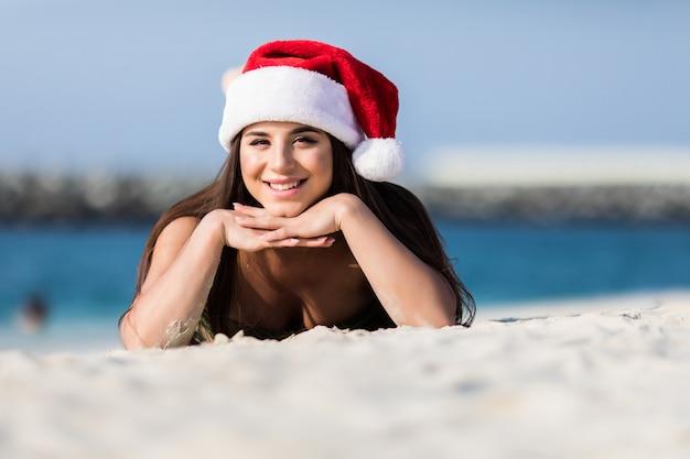 Portrait de jeune femme heureuse sur la plage tropicale portant un bonnet de noel profitant des vacances d'hiver dans une destination exotique. bikini girl bronzer sur la plage de sable blanc, aimer les vacances