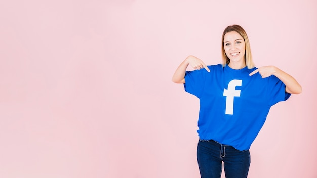 Portrait d'une jeune femme heureuse pointant sur son t-shirt avec l'icône facebook