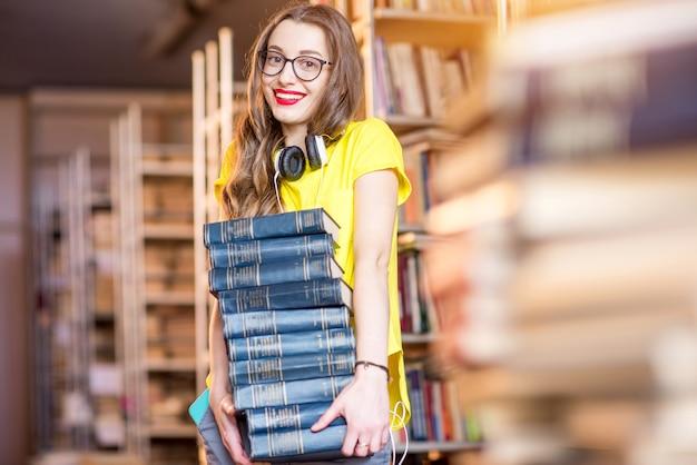Portrait de jeune femme heureuse portant un tas de livres à l'ancienne bibliothèque