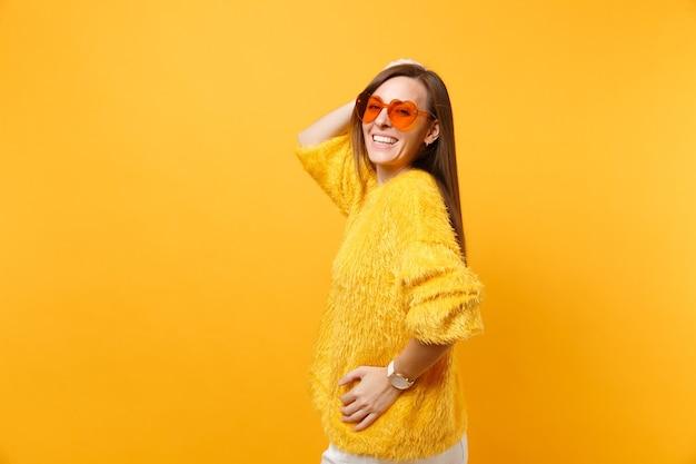 Portrait d'une jeune femme heureuse en pull de fourrure, lunettes coeur orange regardant en arrière mettant la main sur la tête isolée sur fond jaune vif. les gens émotions sincères, concept de style de vie. espace publicitaire.