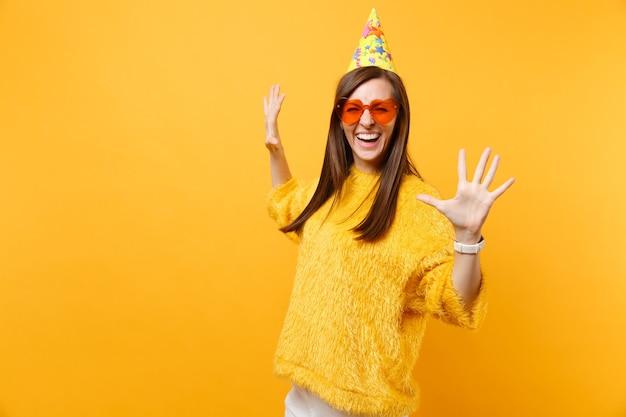 Portrait d'une jeune femme heureuse qui rit dans des lunettes coeur orange, chapeau de fête d'anniversaire écartant les mains isolées sur fond jaune vif. les gens émotions sincères, concept de style de vie. espace publicitaire.