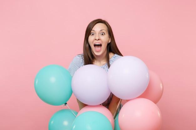 Portrait de jeune femme heureuse ravie avec la bouche ouverte en robe bleue tenir des ballons à air colorés isolés sur un fond rose tendance brillant. fête d'anniversaire, concept d'émotions sincères.