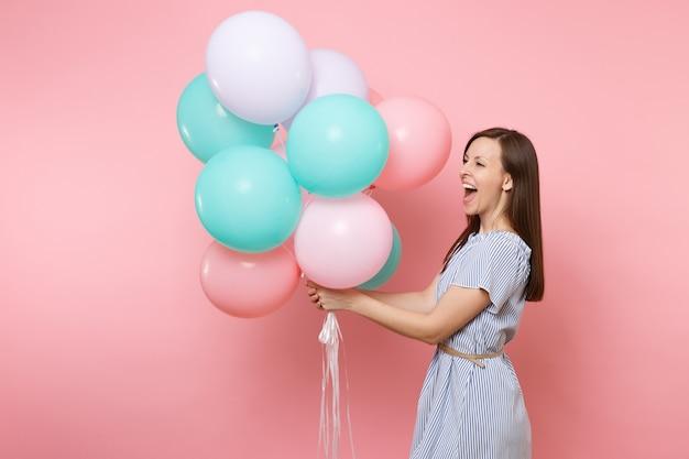 Portrait d'une jeune femme heureuse riant joyeuse vêtue d'une robe bleue tenant des ballons à air colorés regardant de côté isolé sur fond rose vif. fête d'anniversaire, concept d'émotion sincère.