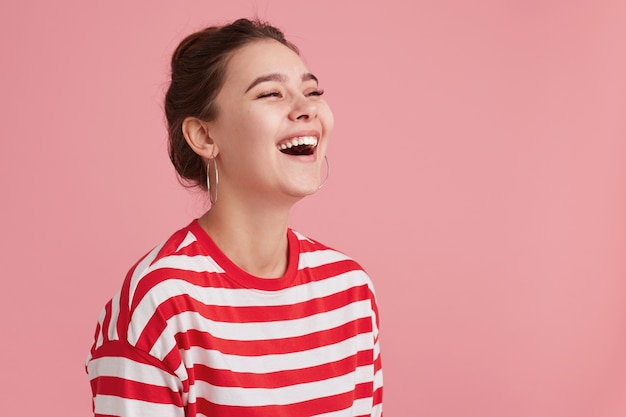 Portrait de jeune femme heureuse en riant avec des taches de rousseur, les yeux fermés, quand elle a entendu une drôle de blague