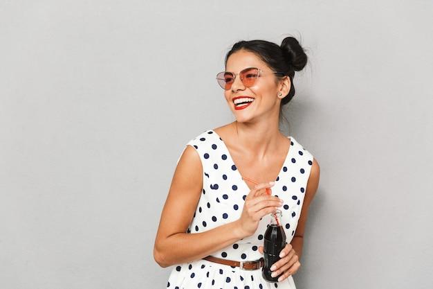 Portrait d'une jeune femme heureuse en robe d'été et lunettes de soleil isolés, tenant une bouteille avec une boisson gazeuse, en regardant l'espace de copie