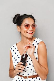 Portrait d'une jeune femme heureuse en robe d'été et lunettes de soleil isolés, tenant une bouteille avec une boisson gazeuse