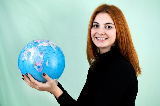Portrait d'une jeune femme heureuse tenant le globe géographique du monde dans ses mains. destination de voyage et concept de protection de la planète.