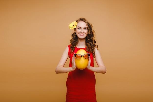 Portrait d'une jeune femme heureuse tenant un melon avec des lunettes. melon avec un sourire