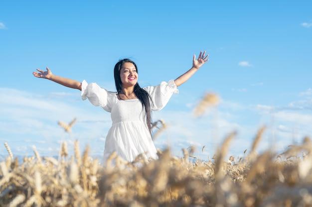 Portrait d'une jeune femme heureuse vêtue d'une robe blanche sur un concept de mode de vie et de bonheur de champ de blé...