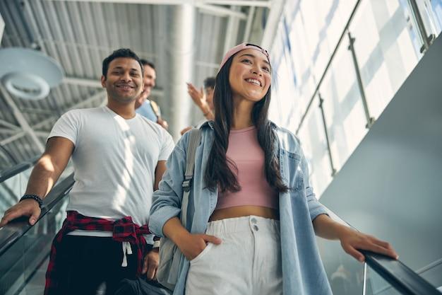 Portrait de jeune femme et homme en vêtements décontractés posant devant l'appareil photo à l'intérieur