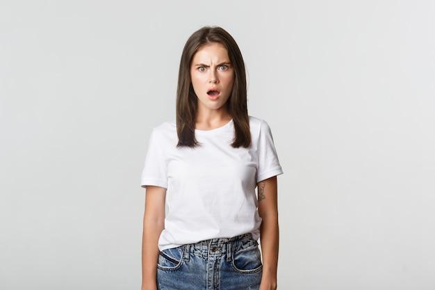 Portrait de jeune femme horrifiée et choquée haletant et fronçant les sourcils frustré