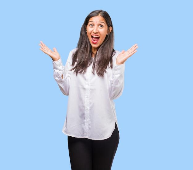 Portrait d'une jeune femme indienne hurlant de joie, surprise par une offre ou une promotion, béante, sautante et fière