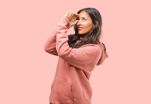 Portrait de jeune femme indienne de remise en forme, regardant à travers une brèche, se cachant et louchant