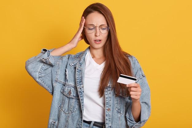 Portrait de jeune femme en jean étonné et chemise blanche, gardant la bouche ouverte, mettant la main sur la tête