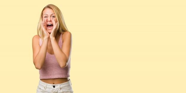Portrait de jeune femme jolie blonde hurlant de joie, surprise par une offre ou une promotion, béante, sautante et fière