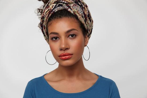 Portrait de jeune femme jolie brune à la peau sombre vêtue de vêtements colorés gardant ses lèvres pliées tout en regardant calmement la caméra, isolé sur fond blanc