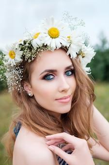 Portrait de jeune femme jolie avec un cercle de fleurs de camomille sur la tête