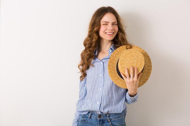 Portrait de jeune femme jolie avec chapeau de paille jeans chemise en coton bleu posant sur mur blanc