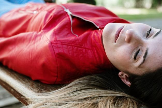Portrait de jeune femme jolie, couchée sur le dos, reposant placidement et détendue.