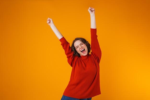 Portrait d'une jeune femme jolie heureuse émotionnelle excitée posant isolée sur un mur jaune.