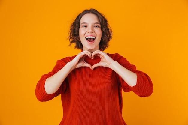 Portrait d'une jeune femme jolie heureuse posant isolé sur un mur jaune montrant le geste du coeur.