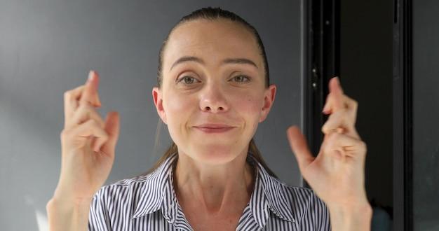 Portrait de jeune femme jolie inquiète avec les doigts croisés et les yeux fermés dans l'attente de la chance.