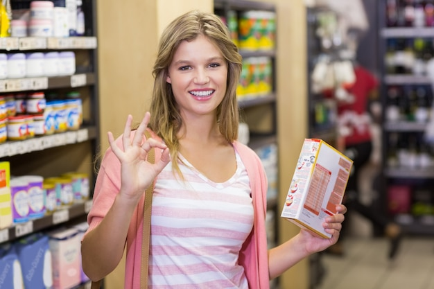 Portrait d'une jeune femme jolie souriante faisant un signe de la main