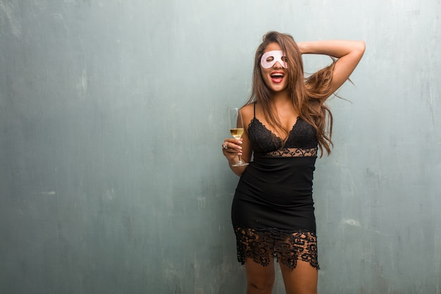 Portrait de jeune femme jolie vêtue d'une robe contre un mur surpris et choqué, regardant avec de grands yeux, excité par une offre ou par un nouvel emploi, concept gagnant