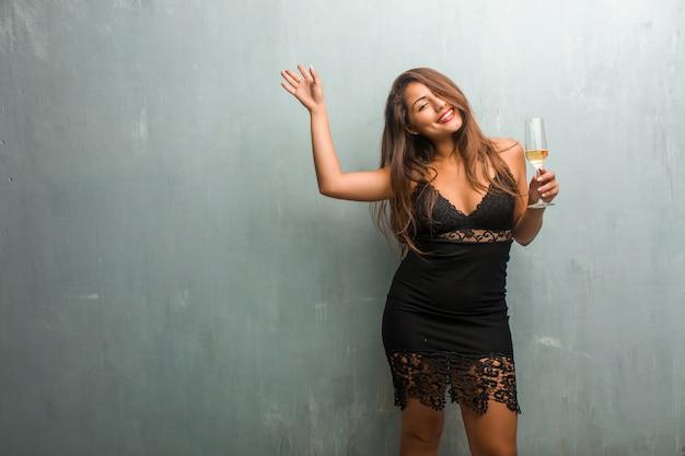 Portrait de jeune femme jolie vêtue d'une robe contre un mur très heureux et excité, rais