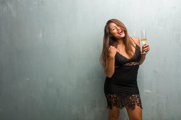 Portrait de jeune femme jolie vêtue d'une robe contre un mur très heureux et excité