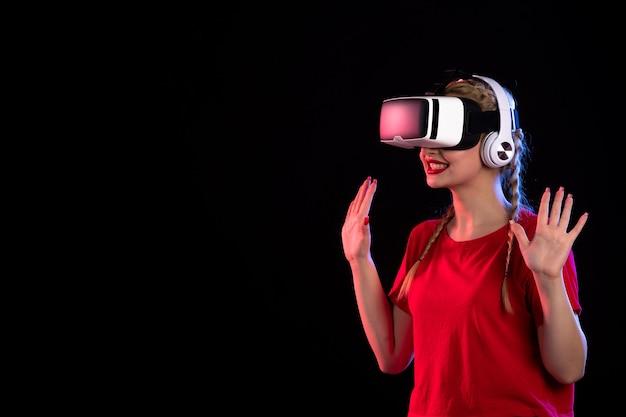 Portrait de jeune femme jouant au vr dans des écouteurs sur un visuel sombre
