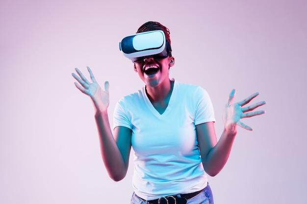 Portrait de jeune femme jouant dans des lunettes vr en néon sur gradient