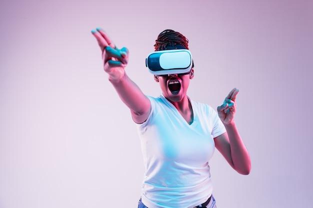 Portrait de jeune femme jouant dans des lunettes vr en néon