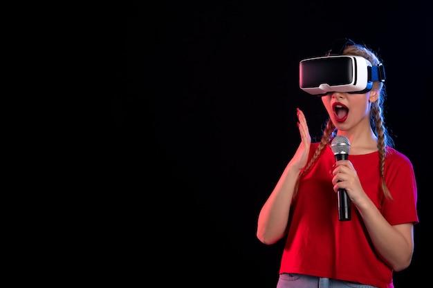 Portrait de jeune femme jouant à la réalité virtuelle et chantant sur un jeu visuel à ultrasons sombre