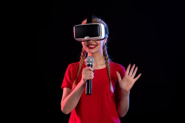 Portrait de jeune femme jouant à la réalité virtuelle et chantant sur un visuel échographique sombre