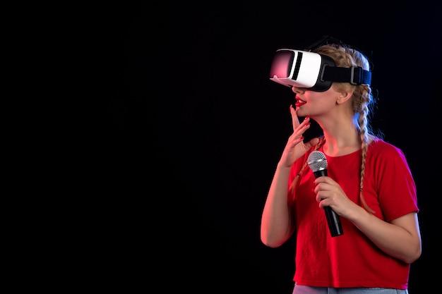 Portrait de jeune femme jouant à la réalité virtuelle et chantant sur un visuel de jeu d'ultrasons de musique sombre