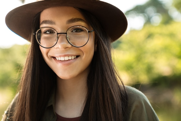 Portrait d'une jeune femme joyeuse aux longs cheveux noirs portant un chapeau élégant et des lunettes marchant dans un parc verdoyant par une journée ensoleillée