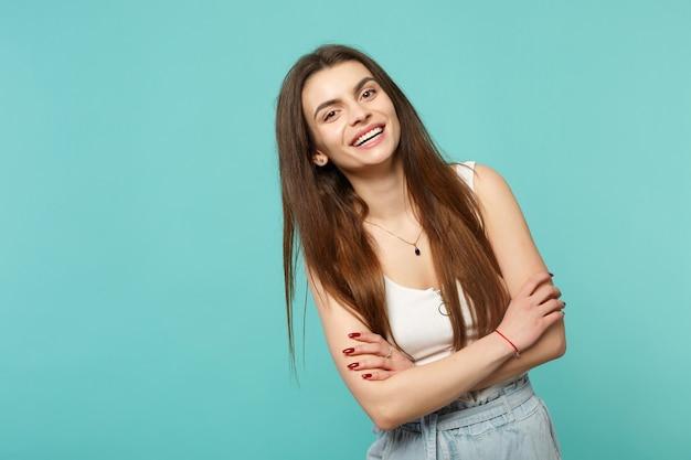 Portrait d'une jeune femme joyeuse dans des vêtements légers et décontractés à la recherche d'une caméra tenant les mains croisées isolées sur fond de mur bleu turquoise. concept de mode de vie des émotions sincères des gens. maquette de l'espace de copie.