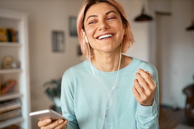 Portrait de jeune femme joyeuse heureuse aux cheveux roses et anneau de nez posant dans un salon élégant portant des écouteurs